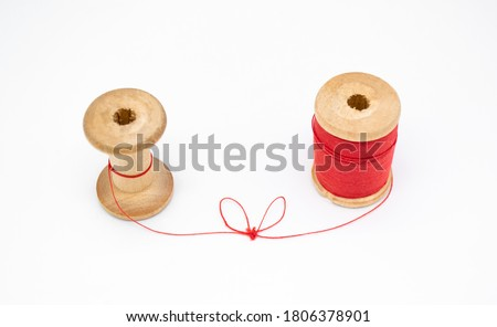 Two wooden spools of thread. One is full, the other almost empty, connected by a single thread with a knot in the shape of a heart. Love and togetherness as a concept, without people Foto stock ©