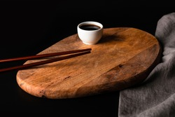Two Wooden Sushi Chopsticks, Bamboo Wood Kitchen Board, White Soy Sauce Gravy Boat And Grey Napkin. Japan Or China Cuisine Still Life On Dark Black Background.