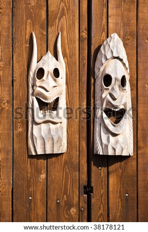 two wooden traditional masks on wood planks