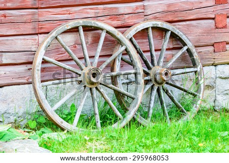 Two wooden wagon wheels leaning against old farm house. Grass in foreground.
