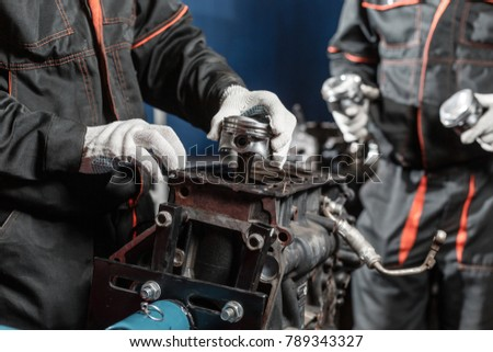 two worker, the mechanic installs a new piston. Disassemble engine block vehicle. Motor capital repair. Sixteen valves and four cylinder. Car service concept.