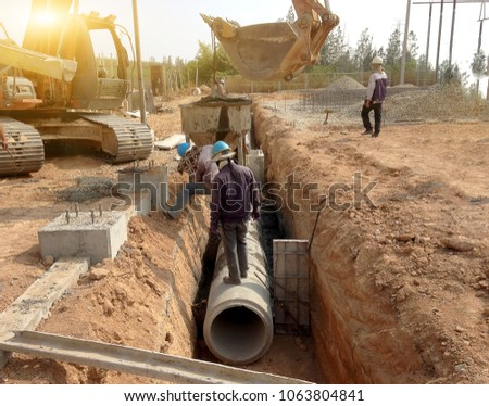 Two workers are installing concrete drains on the side of the road, which is a large power plant construction. Backhoe lifting of concrete pipe drainage system.