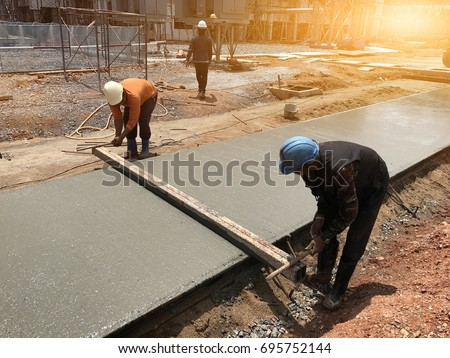 Two workers are using steel box on concrete slabs after pouring concrete,select focus and Light fair.Workers are leveling poured liquid concrete on a steel reinforcement to form strong floor slab. #695752144