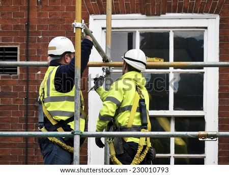 Two workers assembling scaffolding on city building