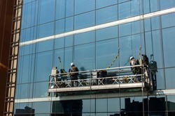 Two workers cleaning window facade of building