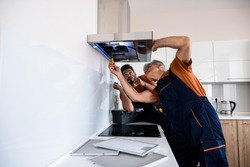 Two workers, handyman in uniform installing or repairing a kitchen extractor, replacing filter in cooker hood. Construction, maintenance and repair concept. Side view. Horizontal shot
