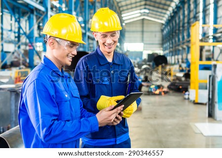 Two workers in production plant as team discussing, industrial scene in background