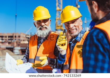 Two workers in reflective vests and hardhats examining building plans and talking on portable radio at construction site