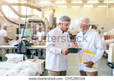 Two workers in sterile white uniforms standing in food factory and looking at tablet. Older one holding folder with statistics.