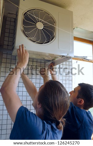 Two workers install air conditioning
