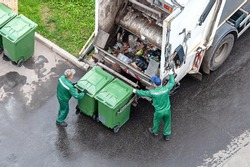 two workers loading mixed domestic waste in waste collection truck