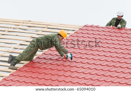two workers on roof at work screw driving metal tile and roofing iron