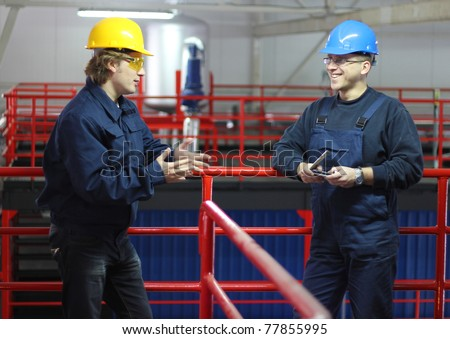 Two workers talking in a factory