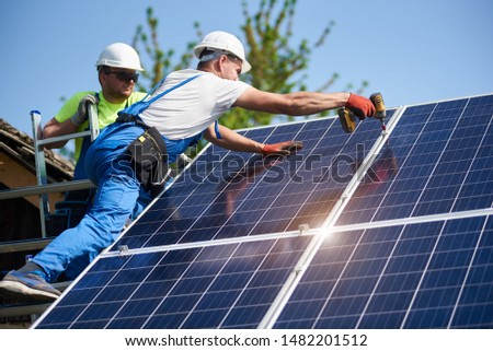 Two workers technicians installing heavy solar photo voltaic panels to high steel platform. Exterior solar system installation, alternative renewable green energy generation concept. Foto stock ©