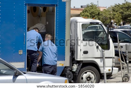 Two workers unload a truck. - stock photo