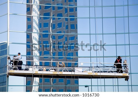 Two workers washing windows in the office building.