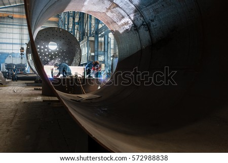 Two workers welding in the interior of a factory manufacturing metallic cylinders for industrial boilers