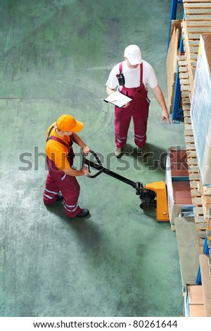 Two workers with fork pallet truck stacker in warehouse loading furniture panels