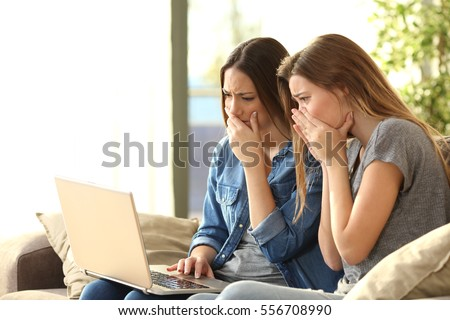 Two worried roommates reading bad news or inappropriate content on line with a pc sitting on a couch in the living room in a house interior #556708990