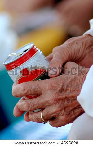 Two wrinkled aged hands of an elderly caucasian white woman holding a can of beer outdoors