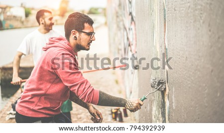 Two writers covering the wall with grey color before painting their picture - Contemporary artists at work - Urban lifestyle, street art and youth concept - Focus on right man face