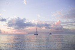 Two yachts in the ocean on a pink sunset.