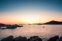 Two yachts moored in a bay as the sun sets over the Mediterranean sea and large granite boulders on the coast of Cavallo Island in the Lavezzi archipelago of Corsica