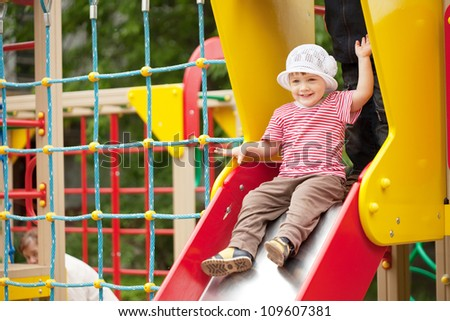 two-year child on slide playground area #109607381