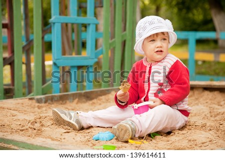 two-year child playing with sand in sandbox