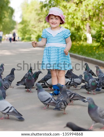 two-year girl with doves  in the city street