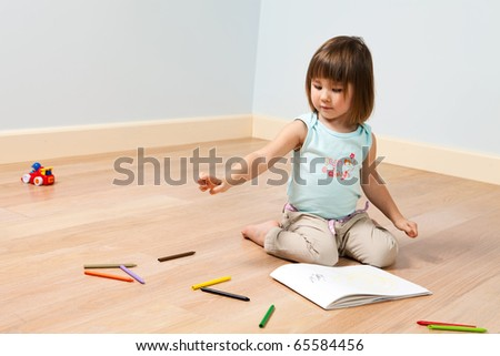 Two year old cute girl paints with color felt-tip pen in a room