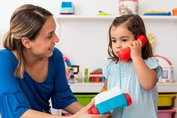 Two-year-old girl and her young kindergarten teacher, both Caucasian, play with a toy phone, talking and listening.