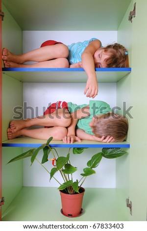 two 5 year old kids sleeping on bookshelves