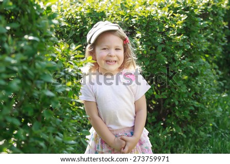 Two year-old laughing girl in corduroy flat cap and skirt at green garden shrubbery background #273759971