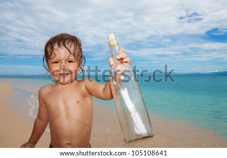 Two years old boy with mayday bottle with message on the beach