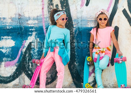 Two 7 years old children wearing cool fashion clothing posing with colorful skateboard against graffiti wall, urban style