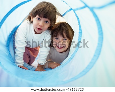 two 2-3 years old girls peeking from blue toy tunnel. Horizontal shape, Copy space