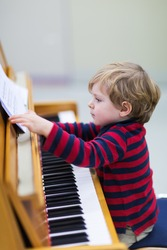 Two years old happy toddler boy playing piano