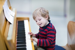 Two years old happy toddler boy playing piano at music school