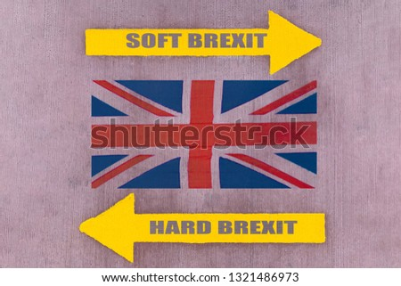 """Two yellow arrow pointers showing the opposite direction, the inscriptions """"SOFT BREXIT"""" and """"HARD BREXIT"""" on a rubber pavement, Union Jack flag between them (concept) #1321486973"""