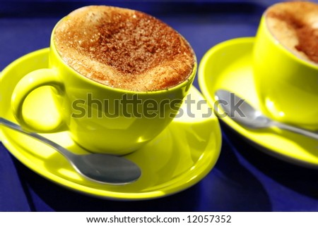 two yellow coffee cups. cappuccino with milk foam  and chocolate powder