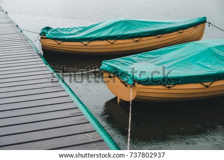 Two yellow covered wood boats tied to the wood pier in the heavy rain on lake #737802937