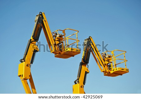 Two yellow hydraulic lift cherry pickers - stock photo