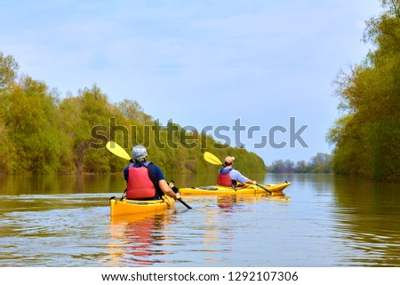 Two yellow kayaks at Danube river at spring. Kayaking in wilderness areas.