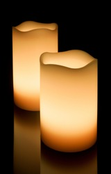 Two yellow LED candles standing on a reflective surface