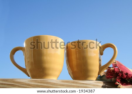 Two yellow mugs on porch against blue sky
