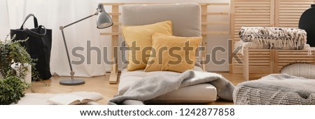 Two yellow pillows placed on futon mattress chair in real photo of bright living room interior with metal lamp, fresh plants, natural materials and book on the floor #1242877858