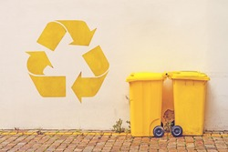 Two Yellow Plastic Recycle Bins on the Street Against White Wall with Recycle Symbol Stencil Graffiti, Toned Image