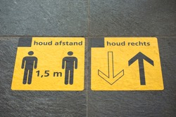 Two yellow sticker signs on platform railway station reminding people to keep social distancing / physical distancing 1,5 meter and to walk on the right side, due to Coronavirus disease (COVID-19)