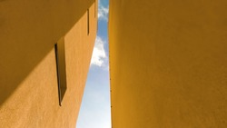 Two yellow symmetrical walls of the house facing the sky and clouds in the form of a tunnel.